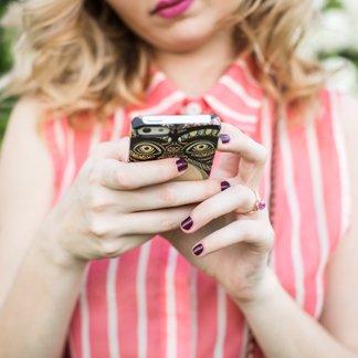 Jeune fille tenant un téléphone cellulaire avec étui d'appareil fait sur mesure