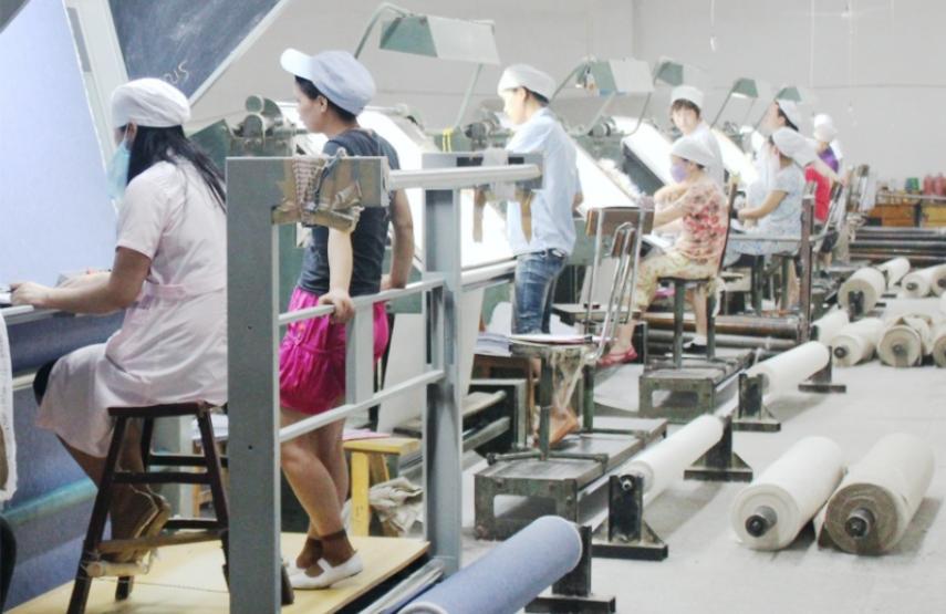 Travailleurs en train d'inspecter du tissu