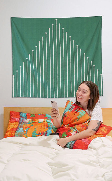 Woman on a bed holding a custom printed cotton canvas pillow