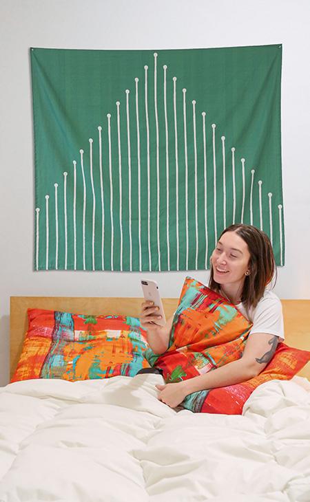 Femme sur un lit tenant un coussin toile coton imprimé sur mesure
