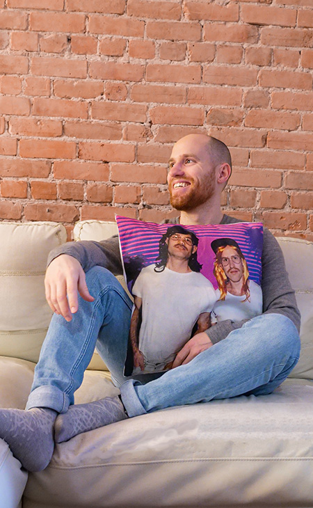 Man on couch holding a custom printed cotton canvas pillow