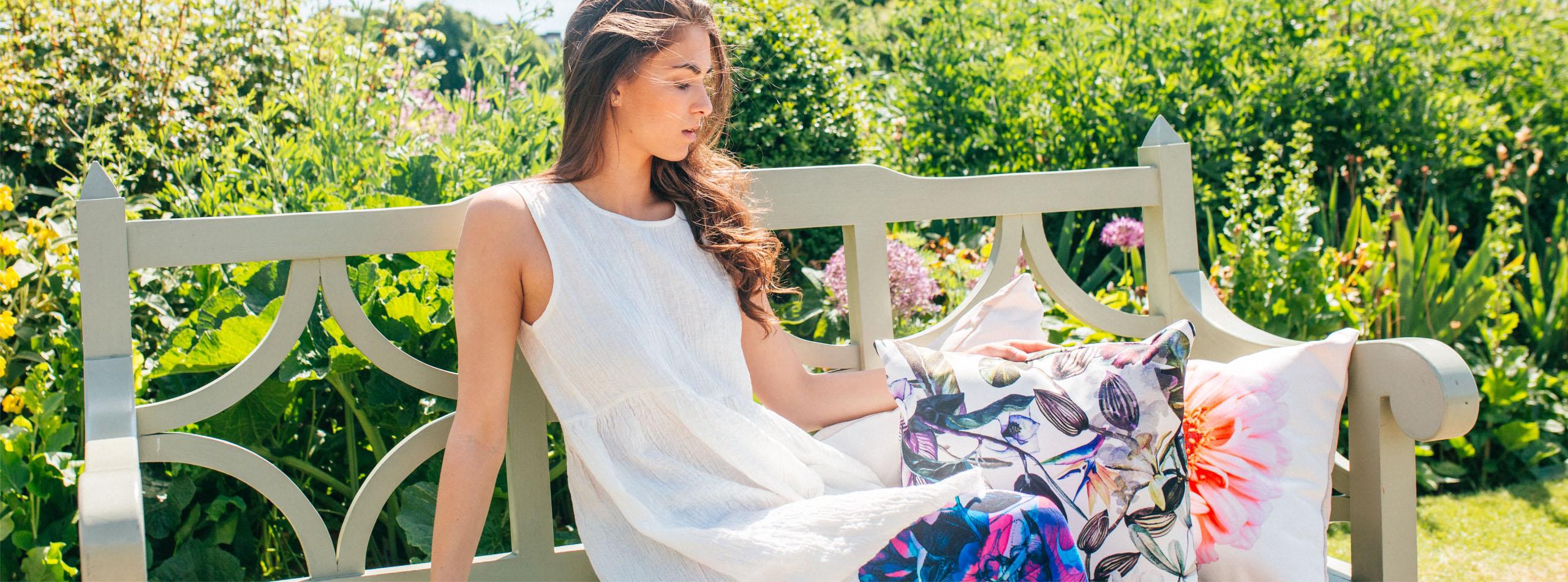 Femme sur un banc à côté de coussins en canvas coton lin imprimés sur mesure