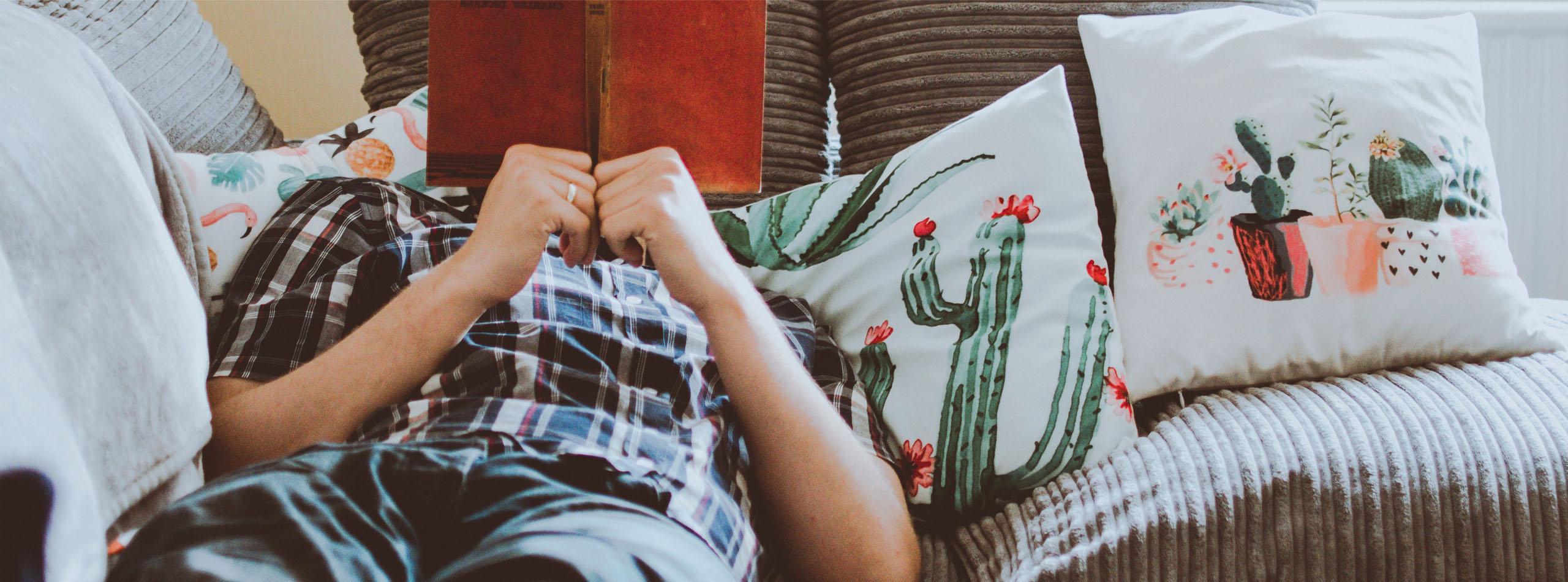 Homme qui lit un livre à côté d'un de coussins en canvas coton lin imprimés sur mesure
