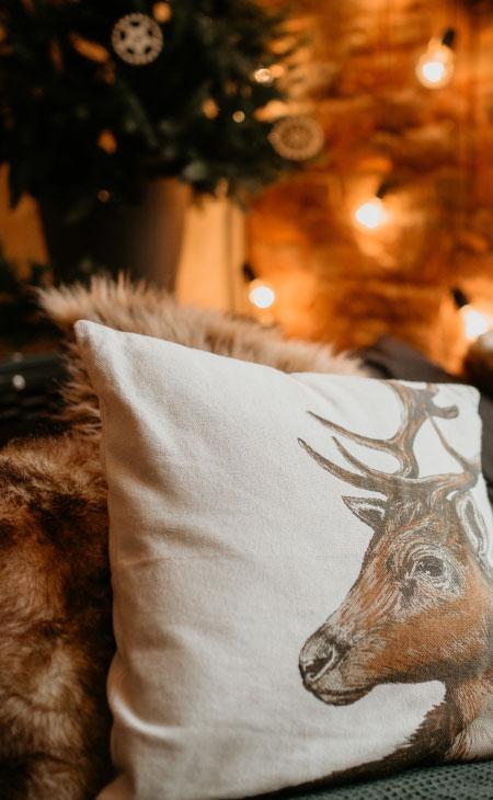 Un coussin coton lin imprimé sur mesure près d'un arbre de Noël