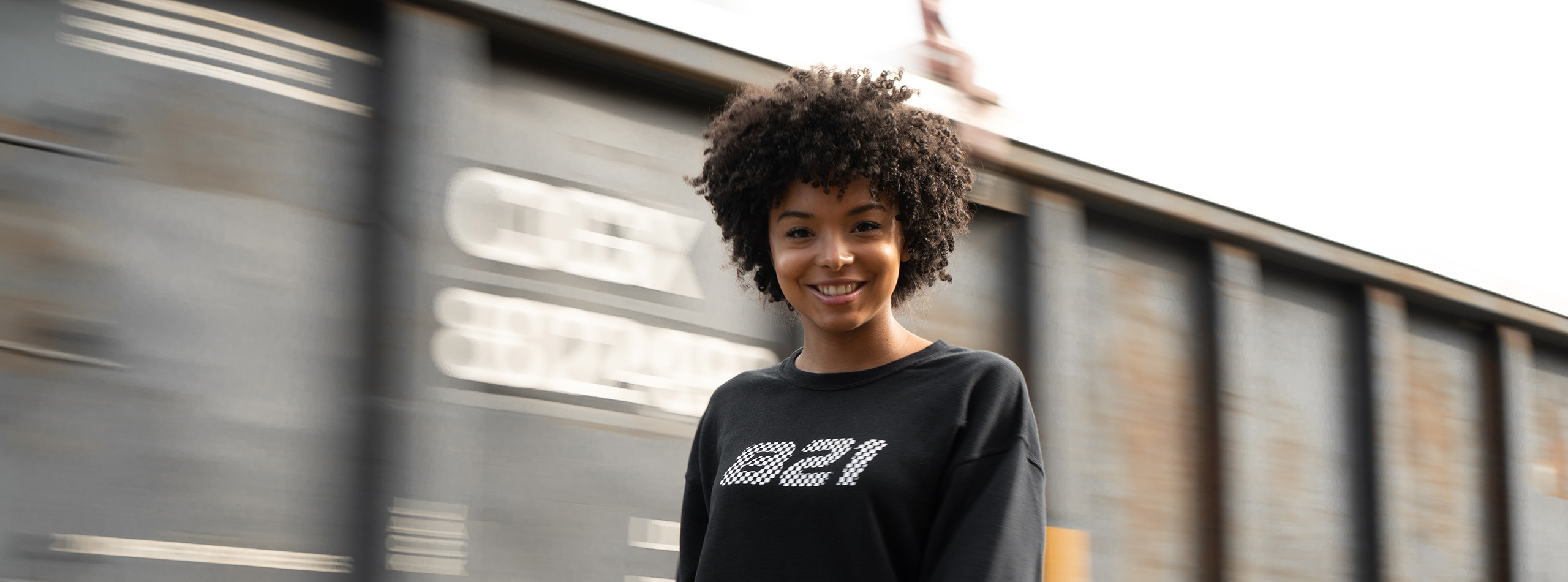 Girl in front of a train wearing a sweatshirt