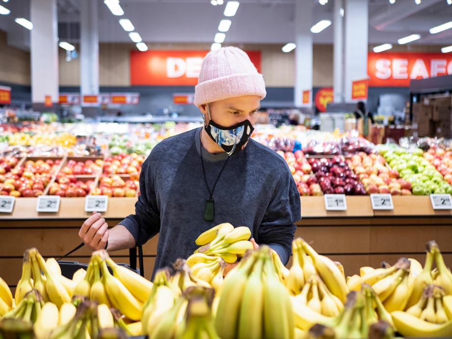 Man with face covering shopping for bananas