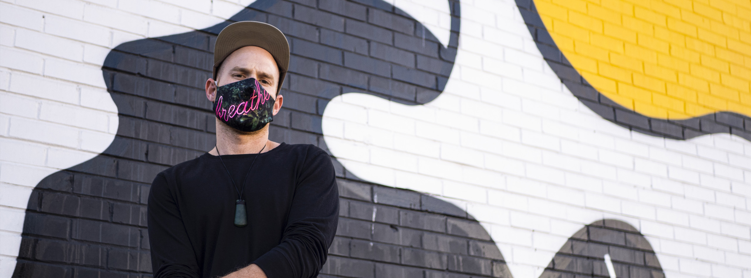 Man with custom printed face covering in front of brick wall